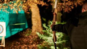 Im Rahmen der DEEPWOOD Weihnachtsfeier spannt ein Mann einen Bogen bei Nacht